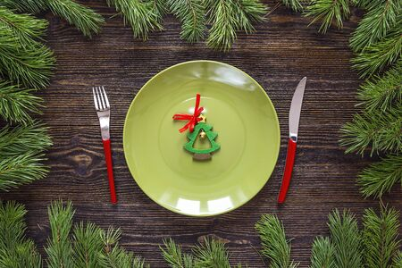 Festive table setting with cutlery and Christmas tree on wooden table. Top view. Christmas tableware.
