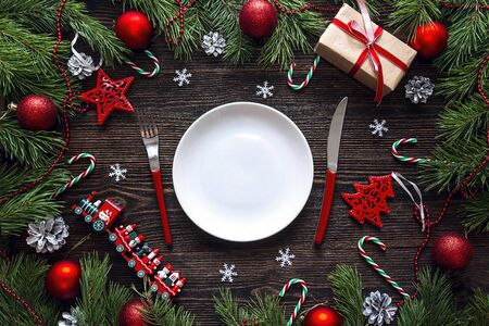 Festive table setting with cutlery and Christmas decorations on wooden table. Top view. Christmas tableware.