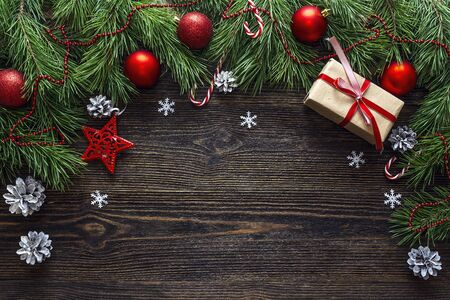 Christmas background with border from pine branches and decorations on dark wooden table. Space for text. Top view.