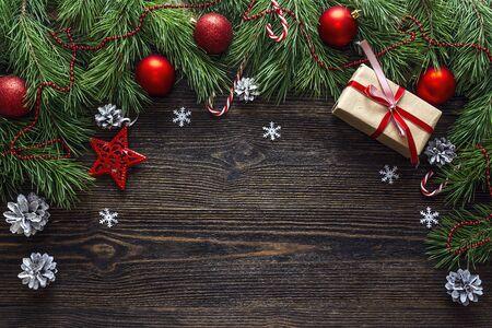 Sfondo di Natale con bordo di rami di pino e decorazioni su tavola di legno scuro. Spazio per il testo. Vista dall'alto.