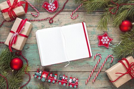 Christmas background with blank notebook, fir branches, decorations and gift boxes on wooden table. Space for text. Top view. Christmas to-do list or wish list. Stock Photo