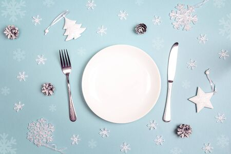 Winter festive table setting with cutlery and white decorations on blue table. Top view. Christmas tableware. Stok Fotoğraf