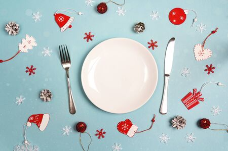 Winter festive table setting with cutlery and Christmas decorations on blue table. Top view. Christmas tableware.