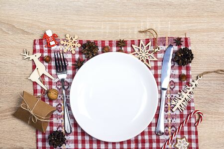 Festive table setting with cutlery, checkered napkin and Christmas decorations on wooden table. Top view. Christmas tableware. Stok Fotoğraf