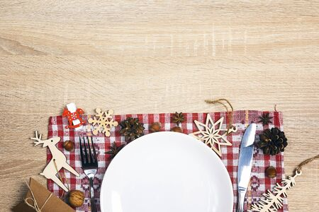Festive table setting with cutlery, checkered napkin and Christmas decorations on wooden table. Top view. Copy space. Christmas tableware.