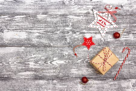 Christmas background with gift box and decorations on grey wooden table. Space for text. Top view. Foto de archivo - 130757779