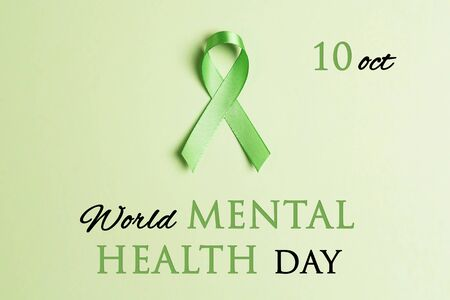 Green awareness ribbon on a green background. World mental health day concept.
