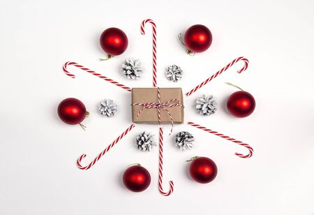 Christmas gift box with candy cane and decorating on white background. Holidays background. Top view.