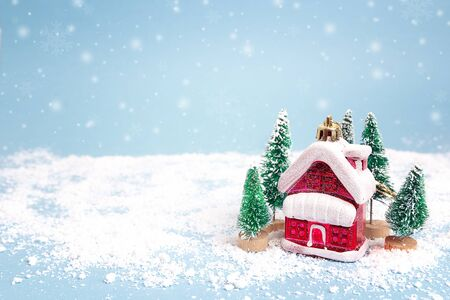 Christmas and New Year miniature  house with fir trees and snowfall on blue background. Copy space for text. Winter card. Holiday and celebration concept.  Stock Photo