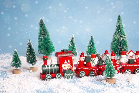 Red Christmas toy train with fir trees and snowfall. Christmas Holiday decorative concept.