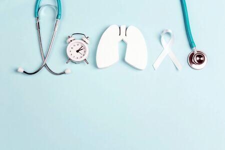 青の白いリボン、目覚まし時計および聴診器が付いている肺癌の意識の背景。テキストのスペースをコピーします。
