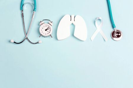Lung cancer awareness background with white ribbon, alarm clock and stethoscope on blue. Copy space for text.