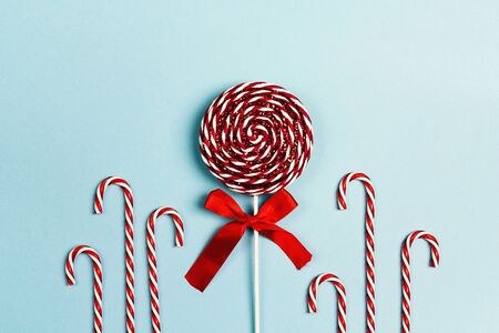 Decorative Christmas lollipop and candy canes on a blue background. Flat lay top-down composition.