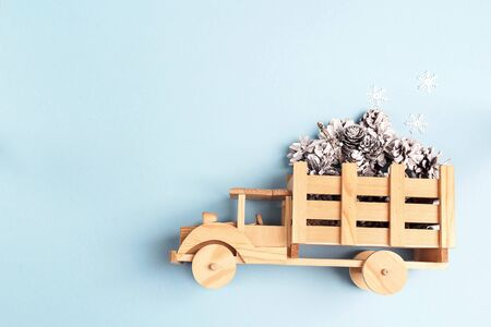 Winter holiday toy truck with snow painted pine cones on blue background. Copy space.