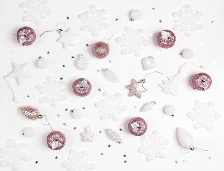 Holiday white and pink decorations pattern on white background. Christmas or New Year top-down composition. Banque d'images