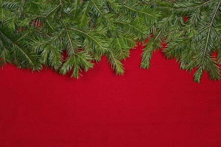Christmas background with fir tree branches  and space for text on red cloth. Top view.
