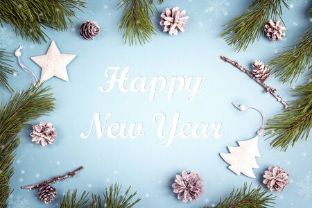 New year greeting message with fir branches and white decorations on the blue background. Top view.
