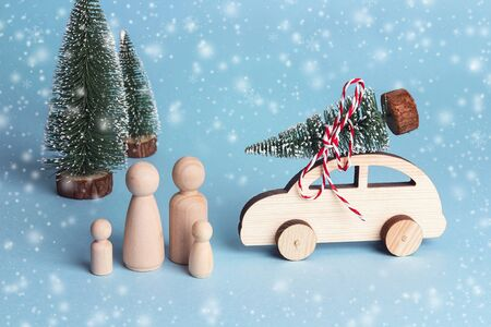 Toy family and toy car with Christmas tree on the roof. Wooden figures of father, mother and children who went by car to the forest for the Christmas tree. Symbolic concept of winter family holidays.