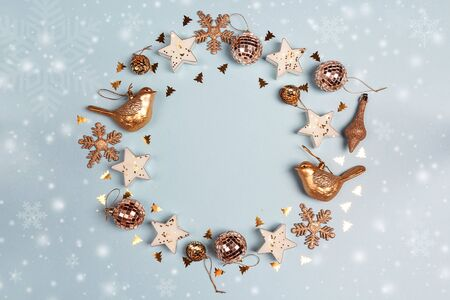 Round frame of golden Christmas decorations with copy space on blue background. Top view, flat lay. Banque d'images