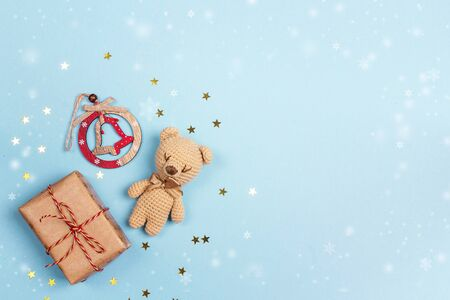 Blue Christmas background with gift box, bell and toy bear. Top-down composition with copy space.