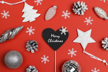 Christmas background with blackboard-heart and white holiday decorations. Top view.