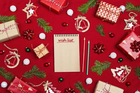 Notebook with a wish list  and Christmas composition of gifts  and decoration on red fabric background.  Flat Lay, top view