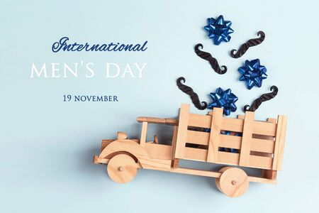 International men's day card with wooden toy truck with mustache and bows in the back on blue background. Flat lay, top view.