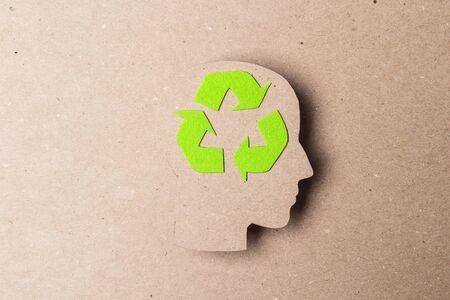 Silueta de perfil de cabeza con símbolo de reciclaje sobre fondo de papel marrón. Pensamiento ecológico. Foto de archivo