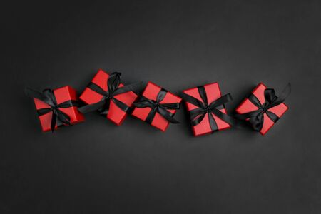 Red gift boxes with black ribbons on a black background. Holiday or black friday concept. Top view with copy space.