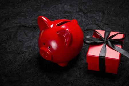Piggy bank and red gift box with black ribbon on a black lace background. Holiday or black friday concept.