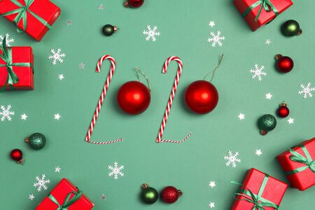 Christmas background with 2020 made from  candy canes and balls. Gifts and decorations on a green background.
