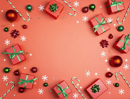 Christmas frame with gifts, decorations and copy space on a red background. Top view, space for text.