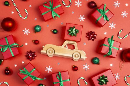 Wooden toy car with gift box on the roof surrounded by Christmas gifts and decorations on a red background. Top-down Christmas composition.