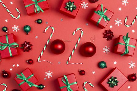 Christmas background with 2020 made from candy canes and balls. Gifts and decorations on a red background.