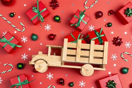 Wooden toy truck with red gift boxes surrounded by Christmas gifts and decorations on a red background.