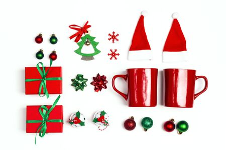 Christmas set with two mugs, santa hats, gifts and decorations on white background. Flat Lay.