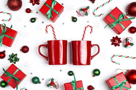 Two red mugs with candy canes surrounded by Christmas gifts and decorations  on white background. Top down composition. Banco de Imagens