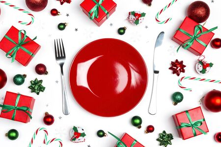 Christmas festive table setting with cutlery, gifts and decorations on white table. Top view. Banco de Imagens