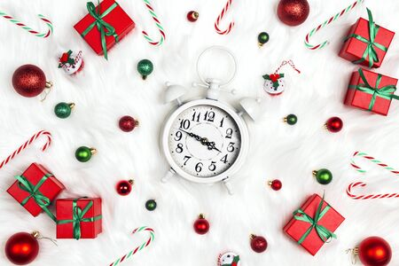 Christmas alarm clock with gift boxes and decorations on a white fur background. Christmas timer. Time to celebrate.
