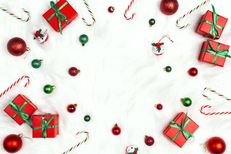 Christmas frame with gifts, decorations and copy space on a white fur  background. Top view, space for text. Banco de Imagens