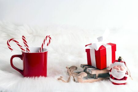 Festive composition with red mug, toy sled with gift box and little santa over fur background. Christmas and New year concept with copy space.