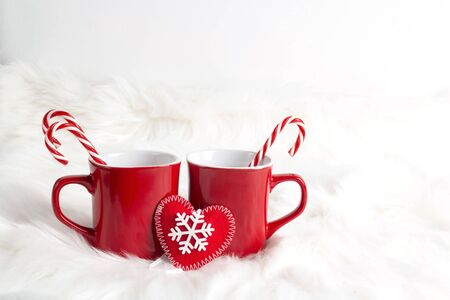 Two red mugs with candy cane on white fur background. Hot drinks: cocoa, chocolate, coffee or tea. Banco de Imagens