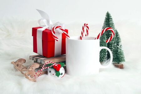 White coffee mug with candy canes and Christmas decorations on white fur background. Space for text or design. Banco de Imagens