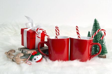 Two red coffee mug with candy canes and Christmas decorations on white fur background. Space for text or design.