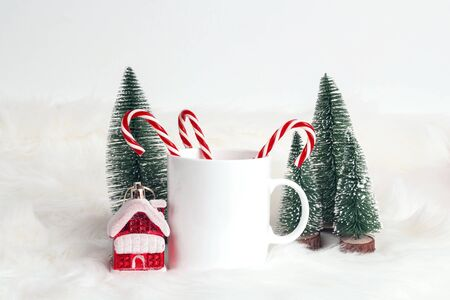 White coffee mug with candy canes, little house and fir-trees on white fur background. Space for text or design. Banco de Imagens