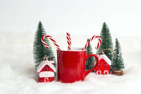 Red coffee mug with candy canes, little houses and fir-trees on white fur background. Space for text or design.