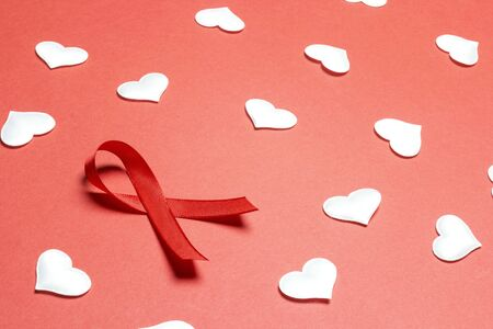 Red ribbon as symbol of aids awareness with white hearts on red background. 1 december World Aids Day concept. Stock Photo