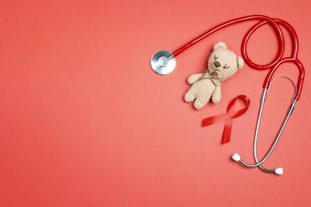 Red ribbon as symbol of aids awareness with children toy bear and stethoscope; on red background. 1 december World Aids Day concept.