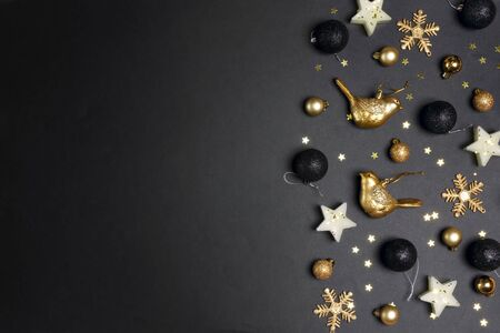 Golden Christmas decorations on back background with copy space for text. Composition of birds, candles stars, snowflakes and balls. Top view, flat lay. Banque d'images
