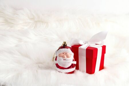 Red gift box with little santa over fur background. Christmas and New year composition with copy space.